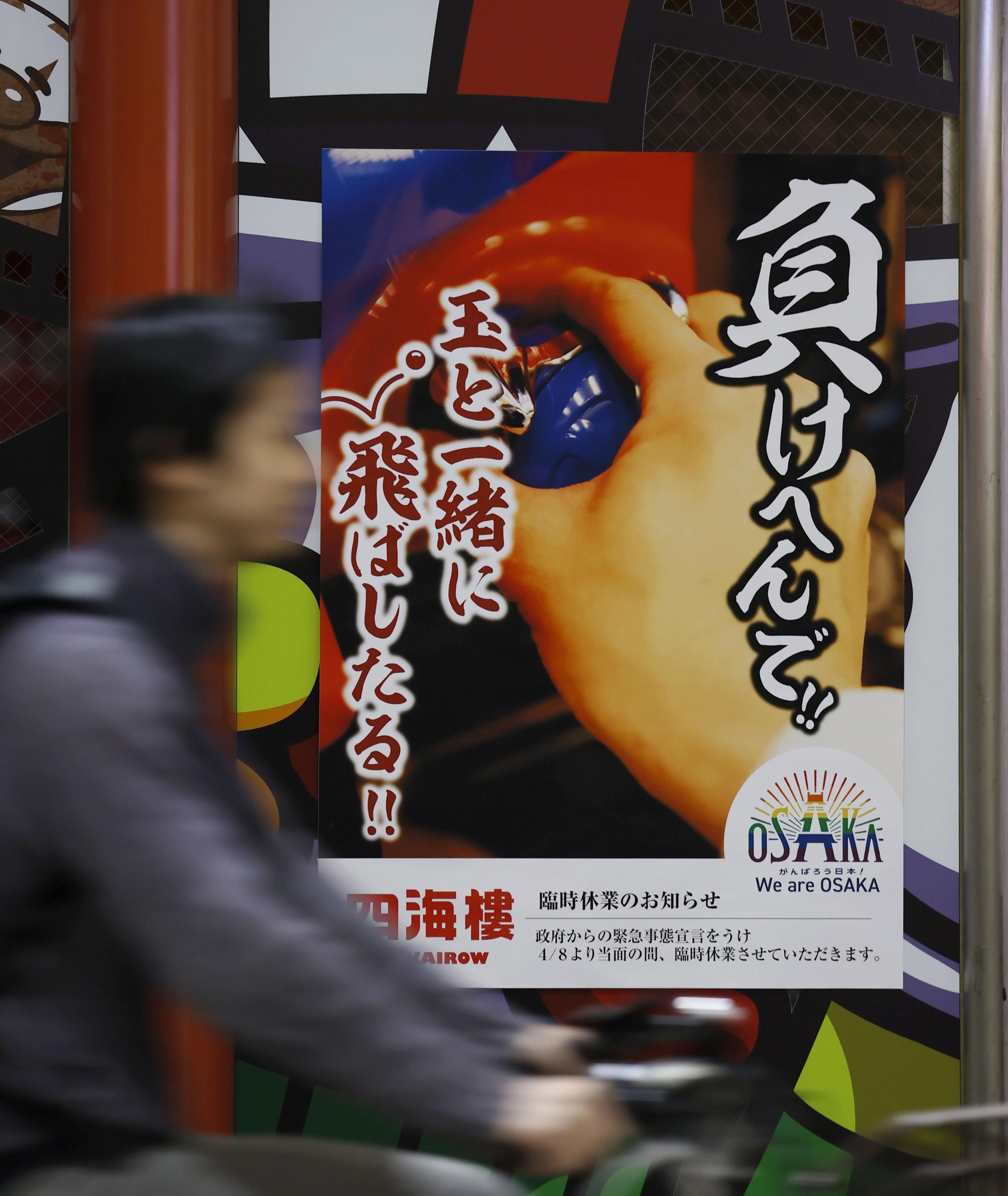 臨時休業中のパチンコ店に張られたポスター=14日午後8時9分、大阪市