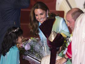 少女から花束を受け取る英国のウィリアム王子(右)とキャサリン妃=14日、イスラマバード(AP=共同)