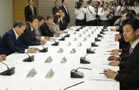 月例経済報告関係閣僚会議に臨む安倍首相(左から2人目)ら=24日午後、首相官邸
