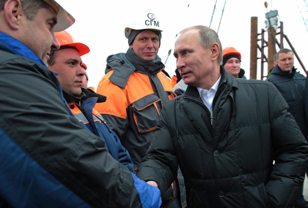 2016年3月18日、クリミアを訪れケルチ海峡の橋の建設現場を視察するロシアのプーチン大統領(右)と作業員ら(タス=共同)