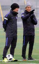 中村ヘッドコーチ(左)と話しながら、トレーニングする選手を見守る城福監督