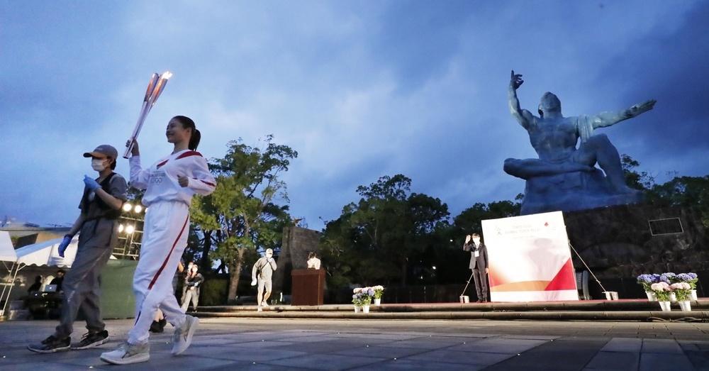 長崎市の平和公園でスタートする聖火ランナーの石原さとみさん。右奥は平和祈念像。無観客で開催された=7日夕