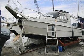 岸壁に衝突し、船首が大破したプレジャーボート=23日午後、広島県尾道市