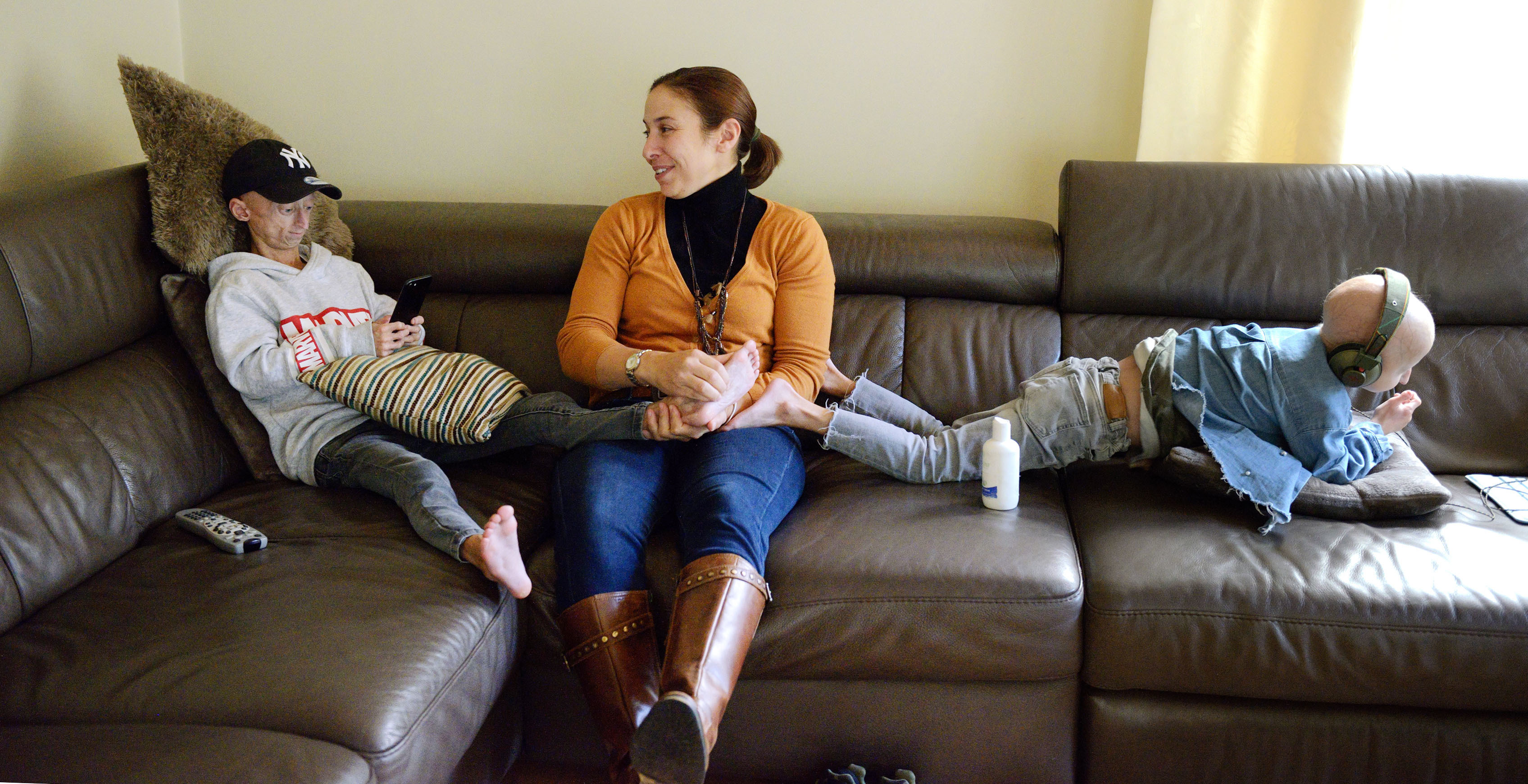 自宅のソファでくつろぐミヒル(左)とアンバー(右)。理学療法士のカタライネ・クレンが二人に関節の痛みを和らげるマッサージを施していた=ベルギー・ディーペンベーク(撮影・澤田博之、共同)