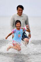 波打ち際で水遊びをする親子=11日午後、宮崎市・青島海水浴場