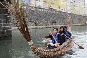 完成した葦船で楽しむ児童ら=長崎市、中島川