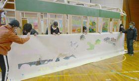ガソリンカーの原寸大模型に設置する風景画を確認する参加者=高松市塩江町、旧上西小