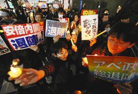 キャンドルを手に安倍内閣の退陣を訴える人たち=23日、東京・永田町で