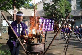 使い込んだばちを火に入れる参列者(京丹波町坂原・道の駅「和」)