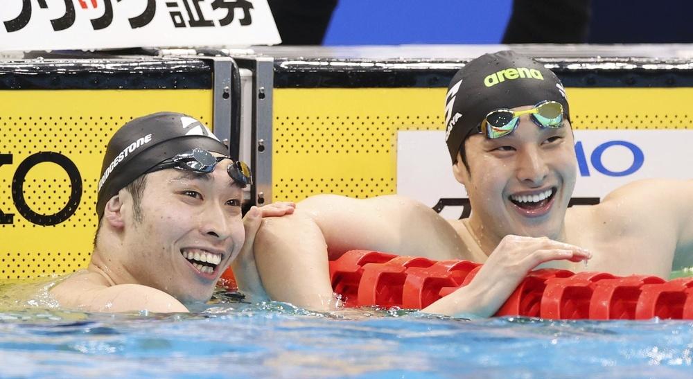 男子200㍍個人メドレー決勝のレースを終え、笑顔を見せる優勝した瀬戸大也(右)と2位の萩野公介=東京アクアティクスセンター