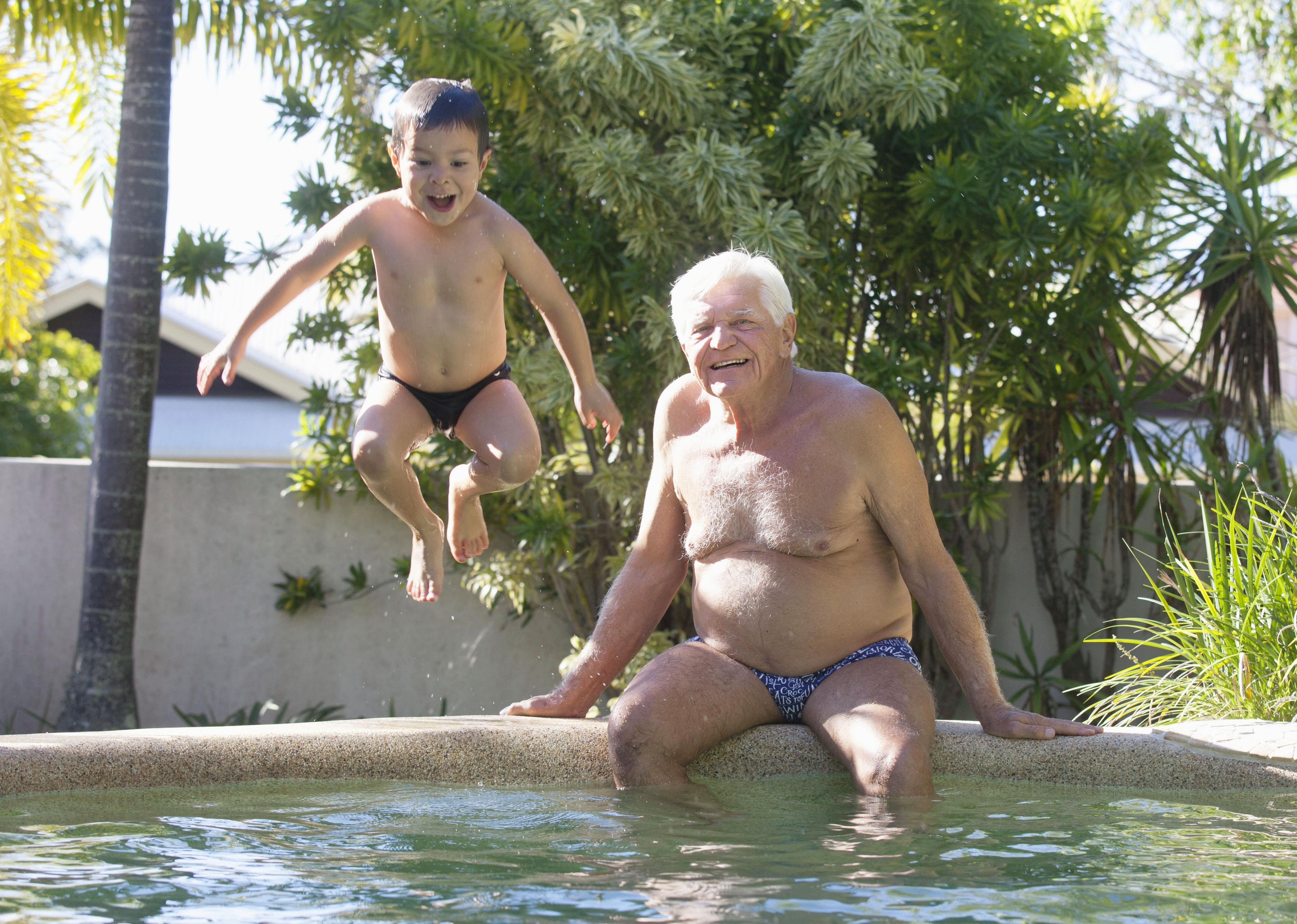 孫タイソン君と自宅のプールで遊ぶジョン・コンラッズ。元気に飛び込む姿を笑顔で見守っていた=オーストラリア・ヌーサ(撮影・金森マユ、共同)