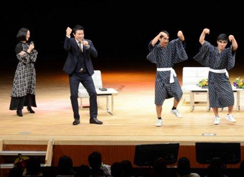 鹿児島実業高校男子新体操部と踊る鈴木亮平さん(左から2人目)と見守る黒木華さん=鹿児島市民文化ホール