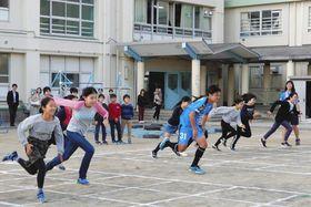 原田選手(中央)と一緒に走る児童たち=高津区の市立坂戸小学校で