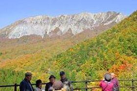 色づき始めた紅葉をバックに写真を撮る観光客ら=鳥取県江府町大河原、鍵掛峠