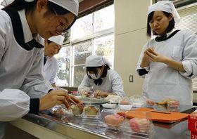 川嶋さん(左奥)の指導でイノシシとウメの花を模した上生菓子作りに挑戦する生徒
