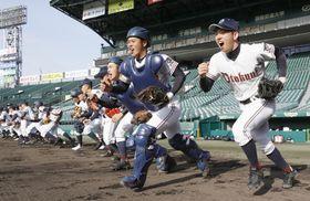 選抜高校野球大会の甲子園練習が始まり、グラウンドへ駆けだす乙訓ナイン