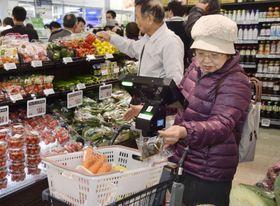 最先端技術を活用したディスカウント店のプレオープンで、レジ機能付きカートを使い買い物する客=11日午後、福岡県大野城市