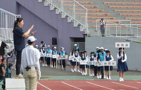 役員・選手団入場時の式典アナウンスを手話する手話通訳者(左)=22日午前、笠松運動公園陸上競技場、吉田雅宏撮影