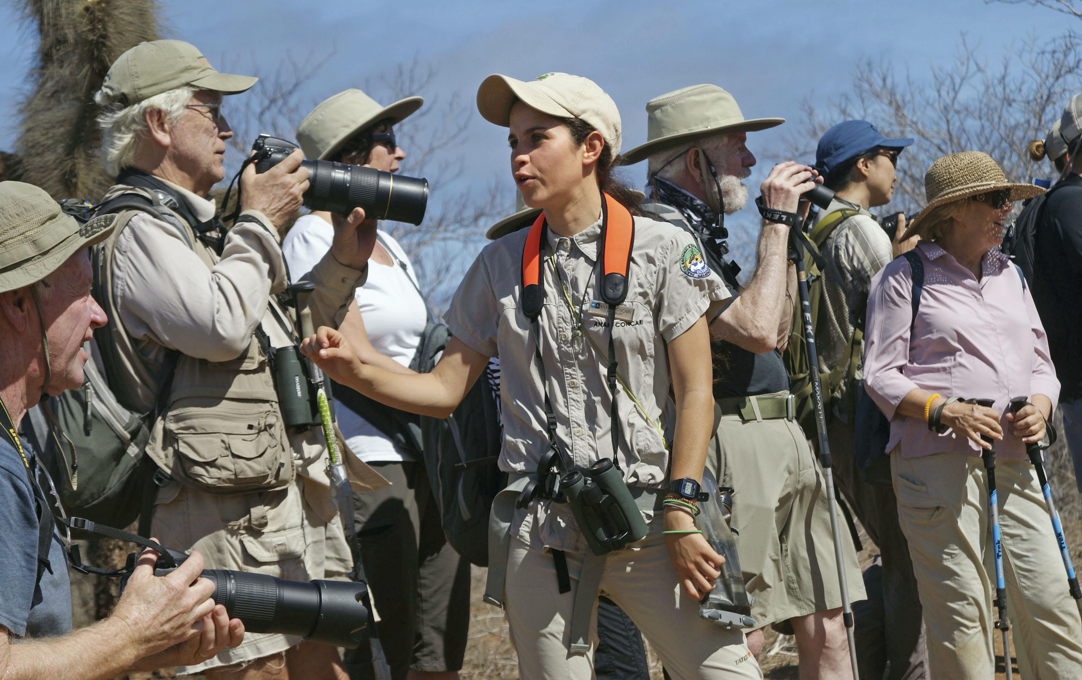 観光客にガラパゴスの自然の価値を説くアナイー・コンカリ(中央)。地元で育った若いナチュラリストだ=11月、ガラパゴス諸島サンクリストバル島(共同)