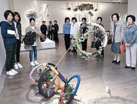 半世紀の節目を彩る生け花作品を楽しむ来場者=金沢21世紀美術館