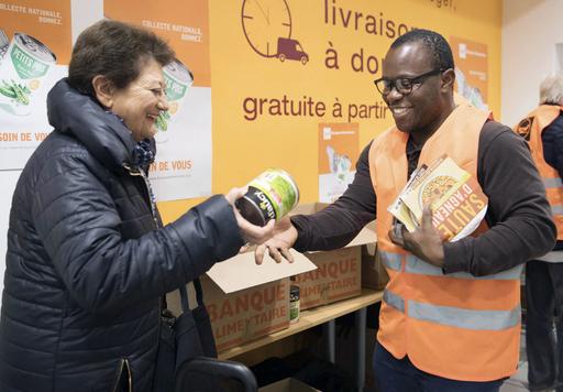 ボランティア活動をするホームレスのウェダ・ジュスタン(右)。スーパーマーケットのレジ先で食品の寄付を受け取る=2018年11月、パリ(共同)