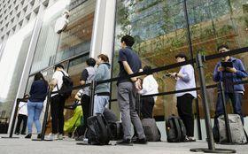 スマートフォン「iPhone」の新型「11」シリーズの発売を待ち、店舗前に並ぶ人たち=20日朝、東京都千代田区