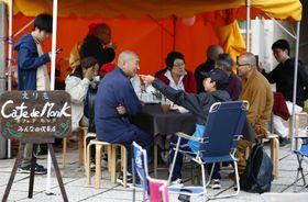 避難所近くに開かれた無料カフェで談笑する僧侶と被災者ら=26日午後、北海道厚真町