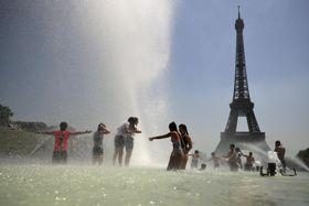 26日、フランス・パリの噴水で涼をとる人々(AP=共同)