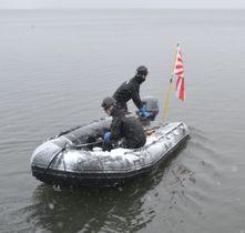 米軍のF16戦闘機が燃料タンクを投棄した小川原湖で、油の拡散状況などの調査に向かう海上自衛隊の隊員=21日午後、青森県東北町