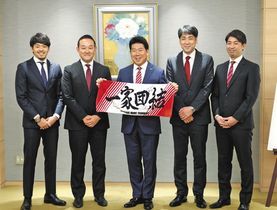 福田市長(中央)を囲んで記念撮影する佐藤新ヘッドコーチ(右)ら=市役所で