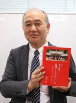 長崎くんちのしくみの改訂版を手にする土肥原さん=長崎市役所
