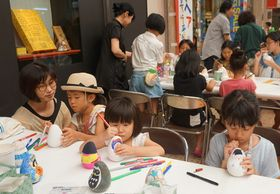 起き上がり小法師の絵付けに挑戦する子どもら=長崎市、浜屋百貨店前