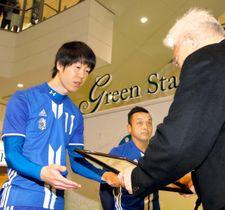 愛媛サッカー大賞に選ばれ、表彰状を受け取る受賞者(左)=11日、松前町筒井