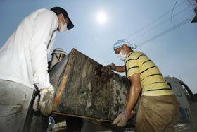 被災した住宅から家財道具を運び出す人=16日午前9時23分、岡山県倉敷市真備町地区