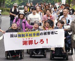 障害者への差別根絶などを訴え、デモ行進する参加者=30日午後、仙台市
