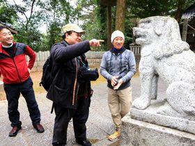 参道狛犬の地域ごとの特徴を観察する研究者や山口狛犬楽会のメンバーら=16日、柳井市