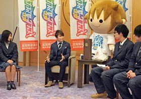 野外音楽イベントの収益を県に寄付し、イベントに協力した高校生と会談する西川さん(中央)=県公館