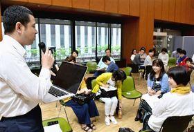 グループ討論で出た意見を発表する参加者=東京都中央区