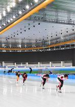 リンクに初めて張られた氷の感触を確かめる選手ら=19日、八戸市立屋内スケート場「YSアリーナ」