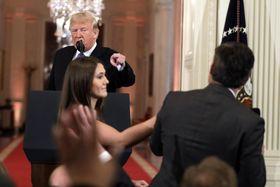 7日、米ホワイトハウスでの記者会見で、CNN記者(右)を指さすトランプ大統領。手前左はマイクを引き取りに来た女性スタッフ(AP=共同)