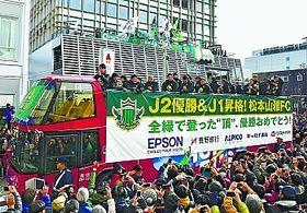 信毎メディアガーデン(奥)を出発し、バスの上から声援に応える松本山雅の選手たち=9日、松本市中央2