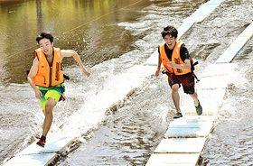 水上に設置された板の上を軽快に走る参加者=川西町・川西ダリヤ園鏡沼