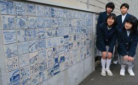 会館の壁面に飾られた陶板を見つめる山科中の美術部員たち(京都市山科区・清水焼の郷会館)