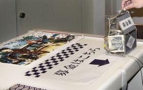 京都アニメーション制作の映画「聲の形」上映会場に置かれた募金箱=13日夜、徳島市