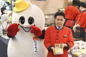 7日、台湾の台北駅にオープンした崎陽軒の店頭で、台湾版シウマイ弁当を手にする粟飯原昌夫総経理(共同)