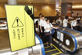 2017年の実証実験でJR東京駅に設置された、エスカレーターで歩かず手すりにつかまるよう呼び掛けるデジタルサイネージ=2017年7月