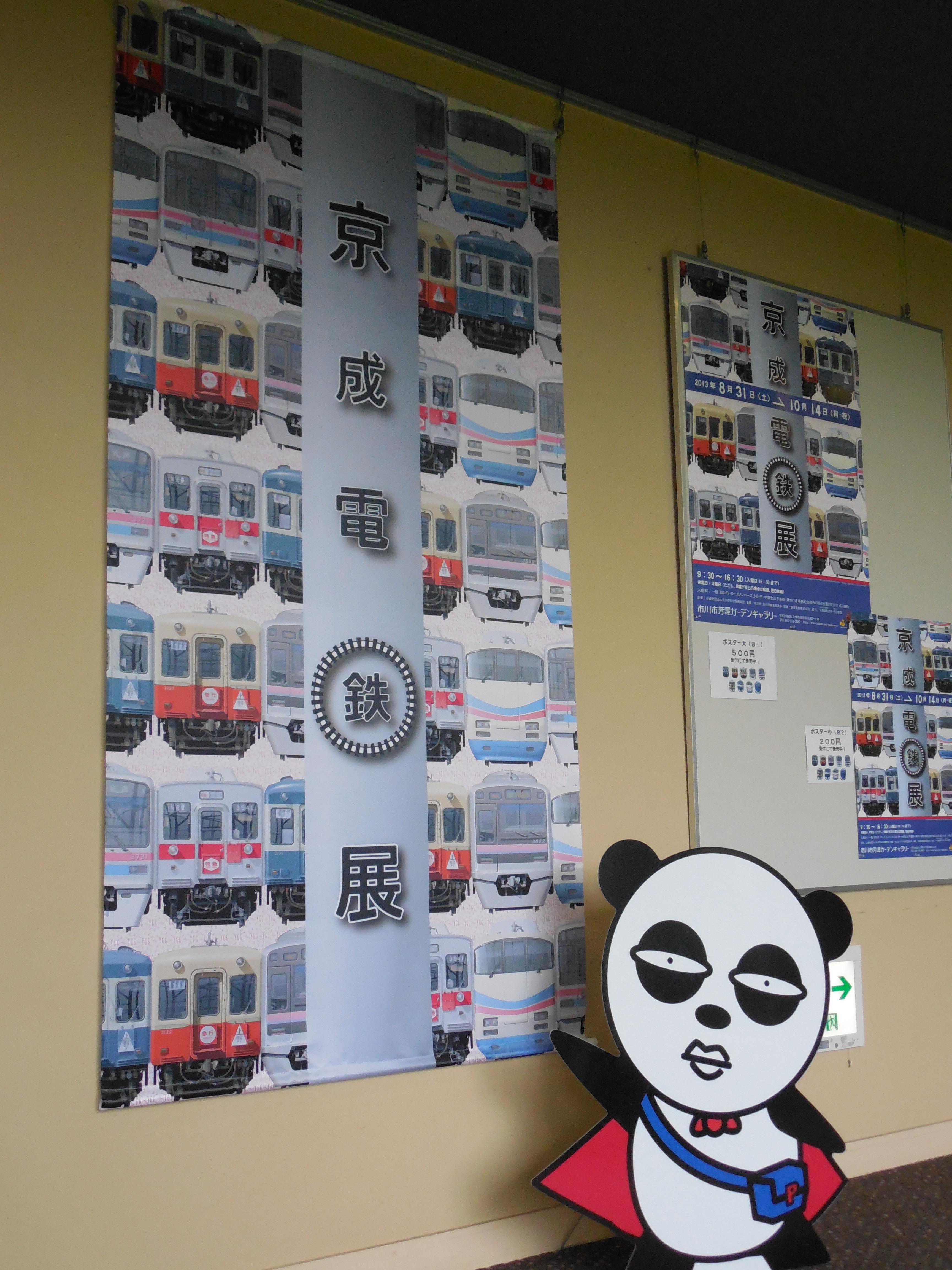 「京成電鉄展」会場で、ポスターを指さす京成パンダ
