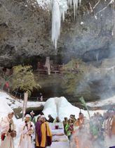 凍った乳穂ケ滝(奥)の前で行われた、凍り具合などで農作物の豊凶を占う神事=17日、青森県西目屋村