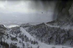 「白根火山ロープウェイ」山頂駅にあるライブカメラが捉えた、本白根山の噴石(中央上)や山肌を伝う噴煙(右)とみられる映像(草津温泉観光協会のユーチューブ映像より)