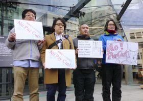 ウーバー・テクノロジーズ日本法人の前で抗議のメッセージを掲げる労組メンバーら=5日、東京都渋谷区